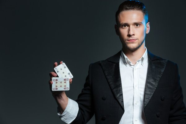 Male magician holding playing cards