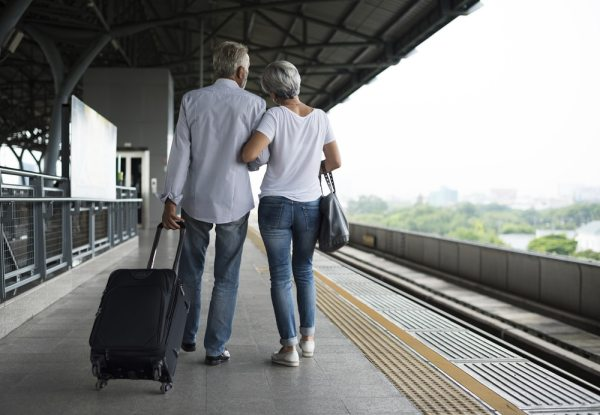 Older couple stood on train platform with suitcase