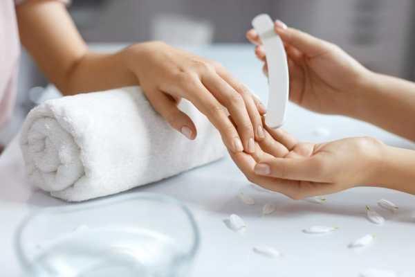 Nail technician buffing womans nails
