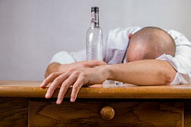 Man slumped on desk with empty alcohol bottle