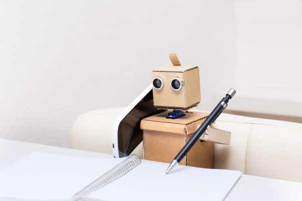 Cardboard robot making a phone call and making notes