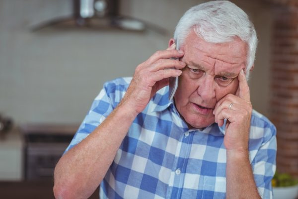Worried elderly man making phone call