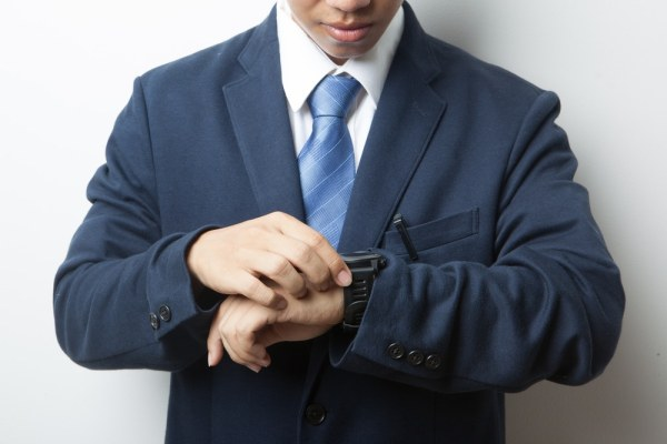 professional man in a suit looking at hi wrist watch