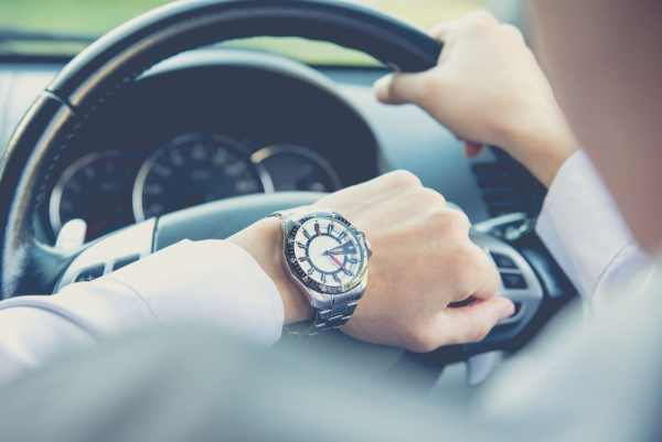 Man checking watch while driving