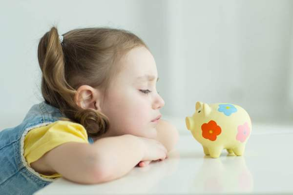 Little girl looking grumpily at piggy bank