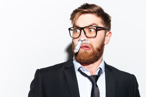 Shocked business man with rolled note and cocaine in his nose