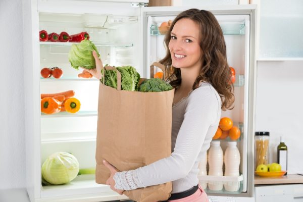 Woman putting groceries in the fridge