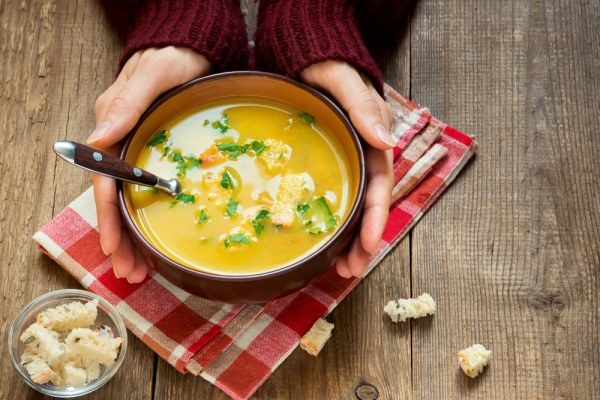 woman warming hands on bowl of soup