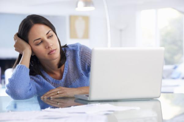 Woman looking fed up while using a laptop