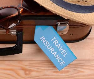 Suitcase and tourist stuff with inscription travel insurance on