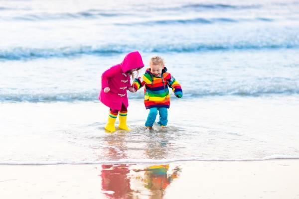 Little girls in wellies playing in the sea