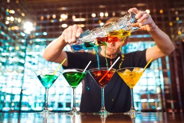 Bartender pouring colourful cocktails