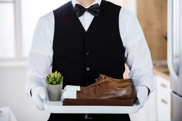 Butler holding tray with clean shoes on