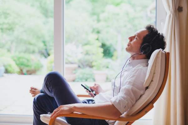 Man relaxing at home listening to music