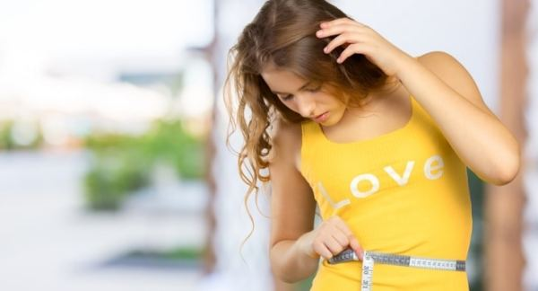 Young slim woman checking the size of her waist with a tape measure