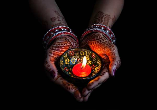 Henna'd hands holding candle for Diwali festival