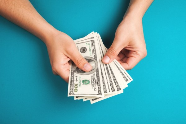 Holding dollar bills on blue background