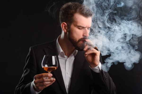 Man smoking and drinking hard liquor