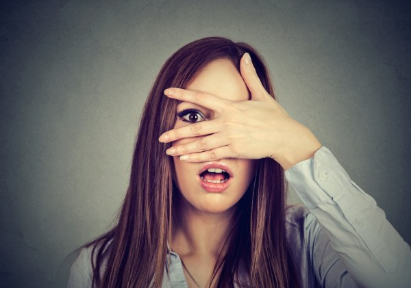 Woman hiding her face behind her hand