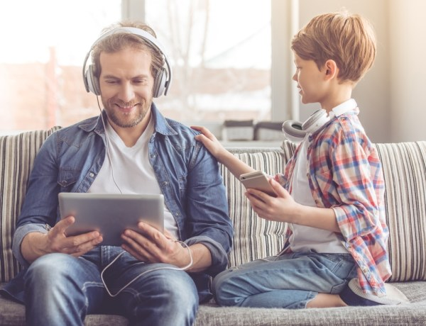 Father using tablet and headphones