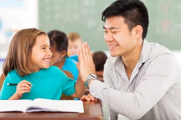 Male teacher high five-ing young student