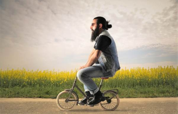 Large man riding very small bicycle