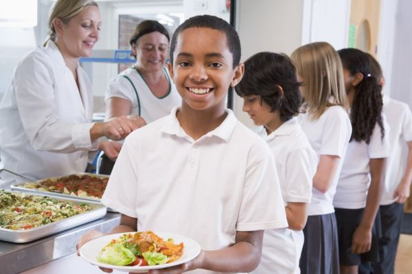 Young boy holding plate of school lunch