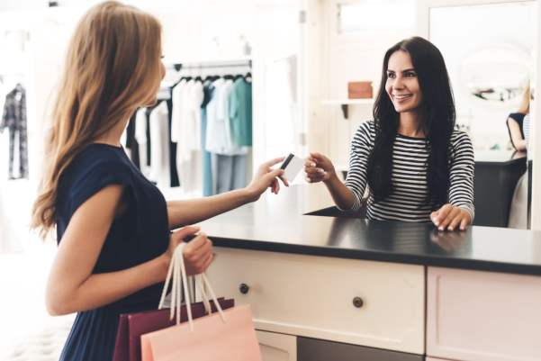 Woman handing her credit card to a cashier in a clothing shop