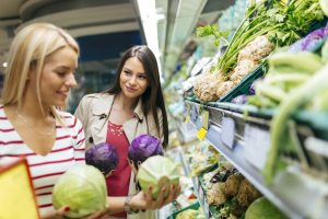 Two young women looking at different cabbages in a supermarket