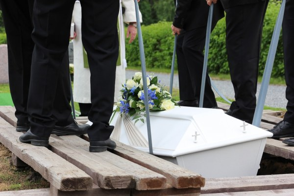 Lowering a white coffin into a grave