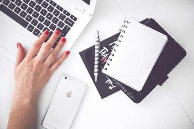 womans hands typing on laptop with notebook beside