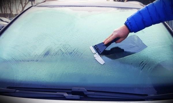 Man scraping ice off his car windscreen
