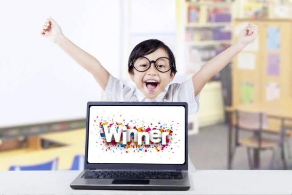 "Little boy celebrating behind a laptop that says ""Winner"" on the screen"