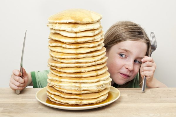 Little girl looking at big stack of pancakes