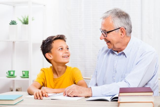 Elderly man tutoring a young boy
