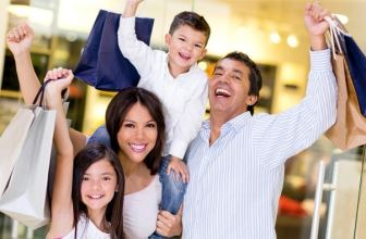 Family laughing together holding shopping bags