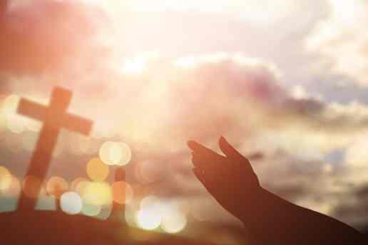 Hands held in worship towards Christian cross