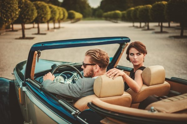 Wealthy couple in open top car