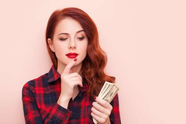 Woman looking at money thoughtfully