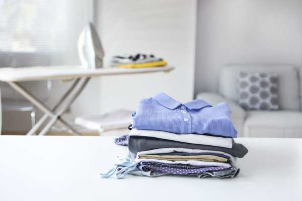 Pile of freshly ironed laundry with iron and ironing board in background