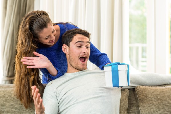 Woman giving shocked man a present