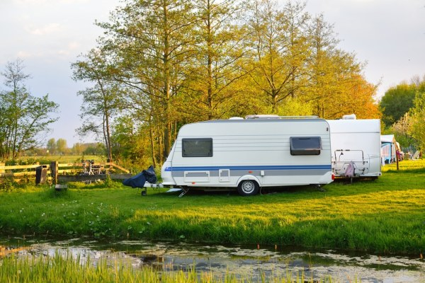 Caravan by a pond during autumn