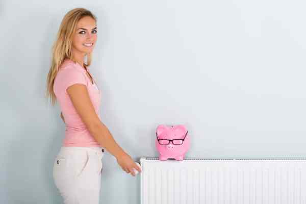 Woman next to radiator with piggy bank