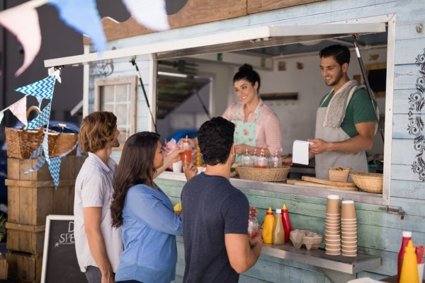 Man and woman serving customers from food truck