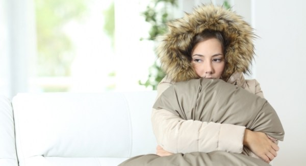 Cold woman weaing a coat inside and looking unhappy
