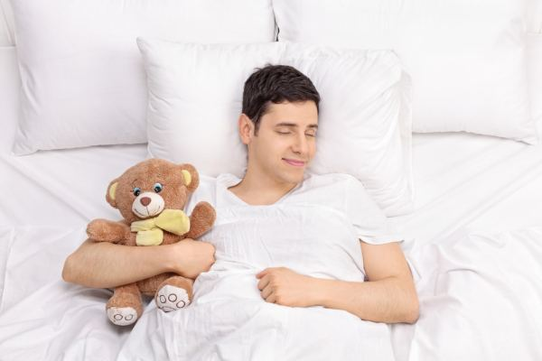 Man sleeping in bed with teddy bear