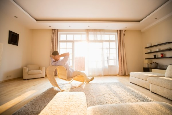 Man relaxing in the sunshine in tidy room