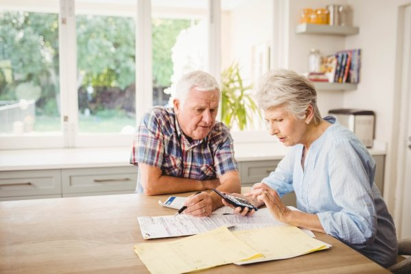 Older couple sat at the kitchen table doing financial planning