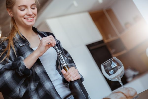 Young woman using bottle opener