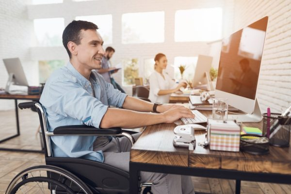 Happy Man in wheelchair working in an office